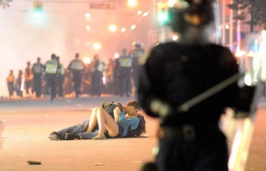 VANCOUVER, BC - JUNE 15: Riot police walk in the street as a couple kiss on June 15, 2011 in Vancouver, Canada. Vancouver broke out in riots after their hockey team the Vancouver Canucks lost in Game Seven of the Stanley Cup Finals. (Photo by Rich Lam/Getty Images)