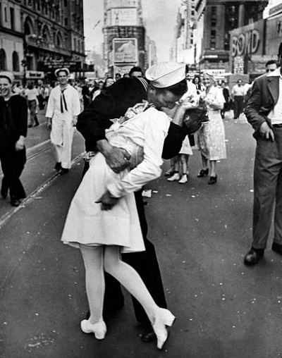A jubilant Amer. sailor clutching a pretty white-uniformed nurse in a back-bending, passionate kiss as he vents his joy while thousands jam the Times Square area to celebrate the long awaited victory over Japan.